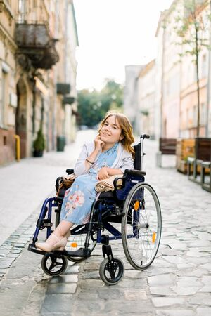 attractive disabled blond young girl in blue dress sitting in a wheelchair, outdoors in the city Foto de archivo - 138396307