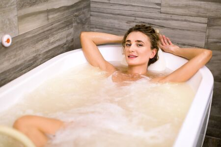 Charming smiling woman relaxing in the bathtub having a hydromassage therapy in the spa center