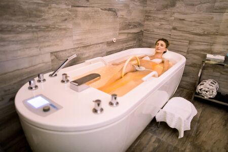 Charming blond woman relaxing while getting hydromassage at spa, lying in bath.