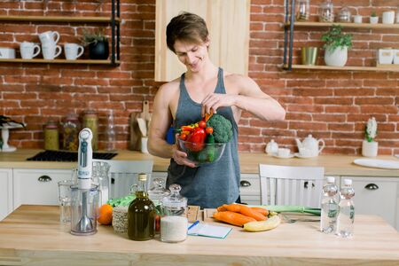 Handsome smiling young man in grey shirt holding a bowl with fresh vegetables on the brick wall background in the kitchen. Healthy and vegan food concept.