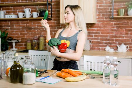 Young and happy woman holding frech cucumber and bowl with fresh healthy vegetables standing on the table with rice, olive oil, carrot, banana and water bottles indoors in the kitchen.