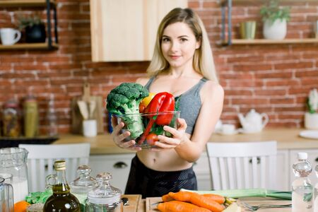 Close-up portrait of smiling young woman holding glass bowl with fresh vegetables while standing at the table with healthy food in modern kitchen. Healthy food concept. Foto de archivo