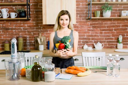 Young and happy woman holding glass bowl with fresh vegetables while standing on the table with healthy food in modern kitchen. Healthy food concept.