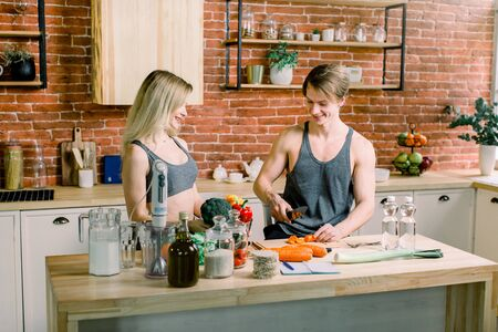 Beautiful young sports people are talking and smiling while cooking healthy food in kitchen at home.
