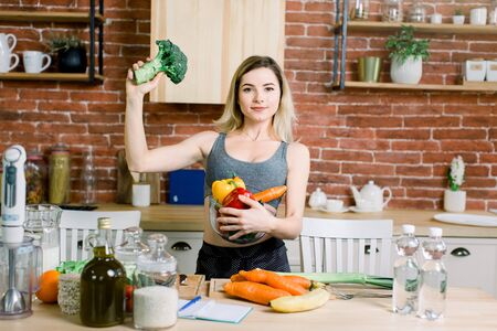 Young and happy woman holding glass bowl with fresh vegetables in left hand and broccoli in right hand while standing on the table with healthy food in modern kitchen. Healthy food concept.