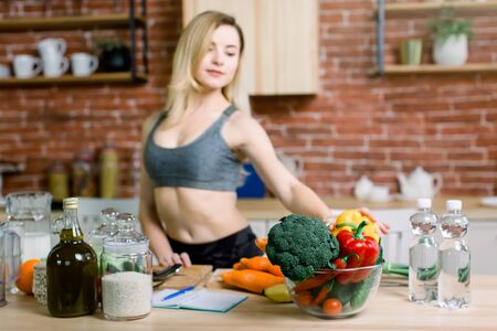 Young and happy woman is ready to eat fresh vegetables and fruits, sitting on the table with healthy fresh ingredients in modern light kitchen. Foto de archivo