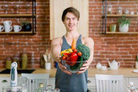 Handsome young cheerful man in sport clothes holding bowl with healthy vegetables and fruits, standing near the wooden table in the kitchen. Healthy and vegan food concept.