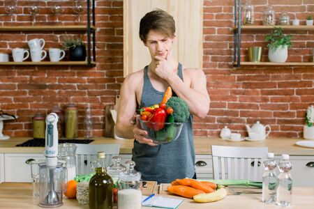 Handsome young sport man holding an healthy fresh vegetarian products in a bowl, fresh raw vegetables and fruits on background in the kitchen. Healthy and vegan food concept. Foto de archivo
