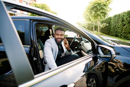Happy smiling African american businessman in smart casual suit speaking on smartphone while getting in the black car on passenger seat