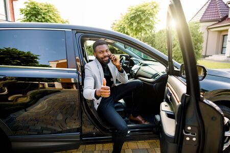 Successful handsome African man businessman and boss sitting in the car, talking on the phone, smiling, looking at camera and showing thumb up. Business concept Stock fotó