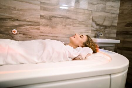 Close up portrait of young beautiful woman lying on special hot spa bed, covered with hot blanket during the mud wrap procedure in the spa. Side view. Archivio Fotografico
