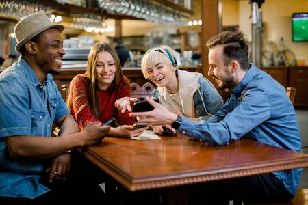 Portrait of cheerful young friends looking at smart phone while sitting in cafe. Mixed race people sitting at a table in restaurant using mobile phone