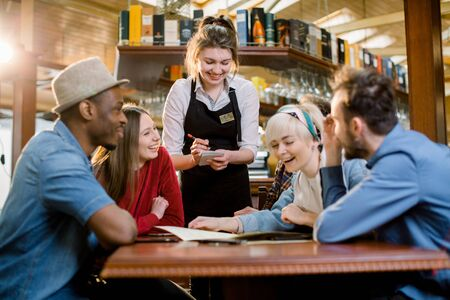 Waitress female welcoming diverse cafeteria pub guests making order waiting staff writing wishes on notepad. Good service dining time, friends meets in public place concept.