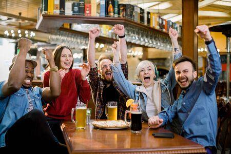Diversos amigos emocionados fanáticos del fútbol celebrando la victoria goles viendo el juego en línea en la televisión en un café apoyando al equipo ganador bebiendo cerveza comiendo pizza juntos