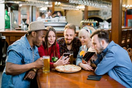 Group of young cheerful friends are sitting in a cafe, eating, drinking drinks. Friends take selfies and take pictures