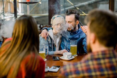 People Meeting Communication Concept. Group of multiethnical students sitting in a cafe bar having fun. Young cheerful couple hugging, kissing and smoking hookah.