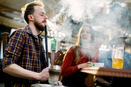 Caucasian young man in casual wear smoking a hookah while sitting at the table in cafe indoors together with friends
