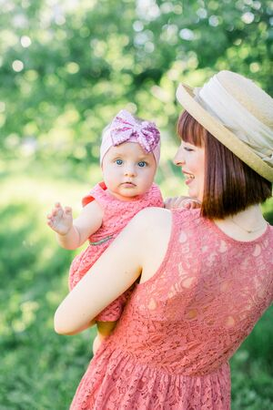 Beautiful Mother with the straw hat And her little daughter outdoors family look in in a pink dress . Outdoor Portrait of happy family. family look. Mother and her daughter in summer park.