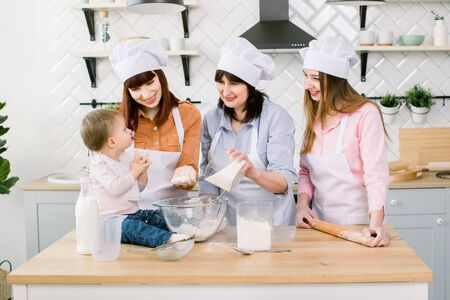 Family with grandmother, two daughters and little baby girl baking at kitchen. Grandmother adds sugar to the dough. Mothers Day concept, family baking Foto de archivo - 139722658
