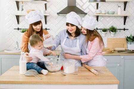 Cute Little Girl and Her Beautiful Mom, Aunt and Grandmother in Aprons and hats having fun While pouring milk to flour and Kneading the Dough in Modern Kitchen at Sweet Home. Women baking at kitchen Foto de archivo - 139722547