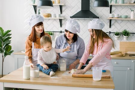 Two sisters, grandmother and little baby daughter cooking holiday pie in the kitchen to Mothers day, casual lifestyle photo series in real life interior Foto de archivo - 139724144