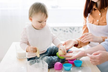 Close-up portrait of cute little baby girl sitting on the dinner table and playing with dough for baking muffins in coloured forms. Mother and grandmother working with dough. Mothers Day concept