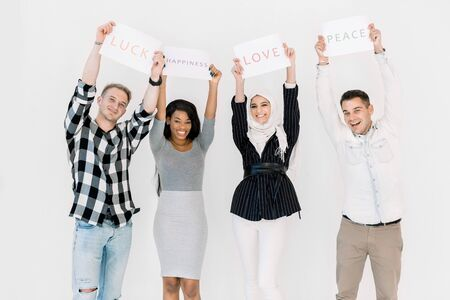 International friendship concept. Group of diverse women and men standing together against white background and holding paper posters with peace love text. Multi ethnic people looking at camera