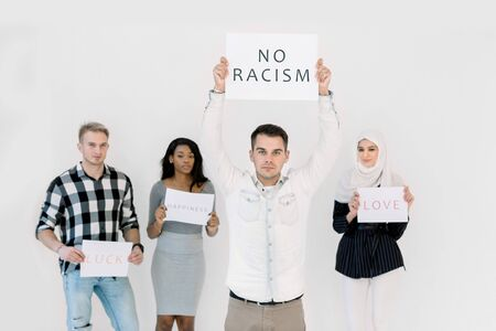 Handsome Caucasian young man protests with a poster, No racism concept, together with three multiethnic friends, African and Muslim women and Caucasian man. Isolated on white