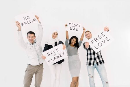 Young four multiethnical activists, volunteers, ecologists with banners shouting about racism, saving earth, no war, equal rights, standing isolated on white background