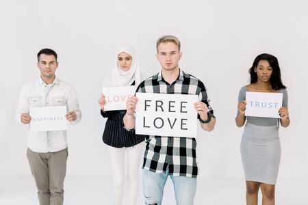 Young handsome Caucasian man with poster for LGBT rights, free love. His multiethnic friends standing with posters on the backgorund