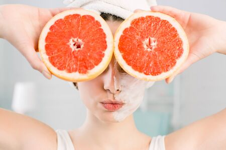 Young sexy woman posing with kissing face and slices of red grapefruit on her face on light background. Natural cosmetics, skincare, wellness, facial treatment, cosmetology concept.