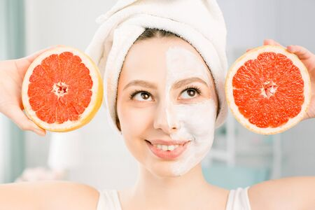 Beautiful young woman with white facial mask and grapefruit halfs on light background. Happy woman with a white towel on her head holding a grapefruit in her hand