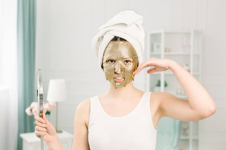Gold mask cosmetic procedure in the beauty salon. Attractive Sexy Girl With White Towel Touching Face And Golden Mask On Face, Holding a Mirror.