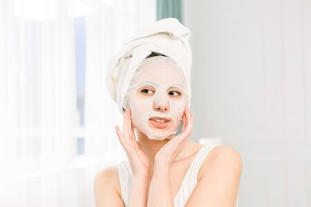 Woman Beauty Face. Closeup Of Smiling Young Female With Fresh Natural Makeup applying Textile Sheet Facial Mask. Portrait Of Attractive Happy Girl With White Cosmetic Mask.