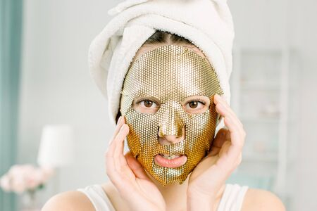 Portrait Of Beautiful Young Female in white towel on the head With Cosmetic Sheet Gold Mask On Beauty Face. Skin care concept.