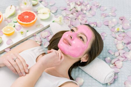 Young healthy woman in spa making treatments and face mask, natural cosmetics and fruits around her. Young woman in a spa with algae facial mask.