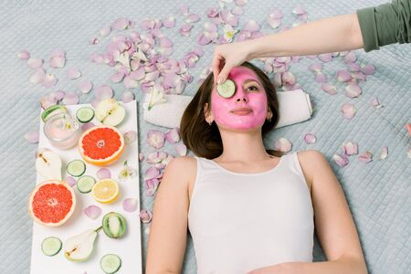 Beautiful young woman receiving spa treatment with pink cosmetic mask, and slices of cucumber on her eyes, skincare, antiaging, acne 스톡 콘텐츠