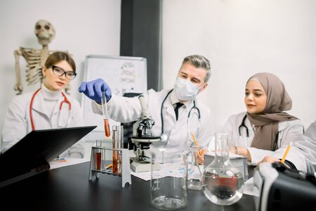 Medicine, genetics, immunology, microbiology concept. Multiethnic group of scientists, Caucasian man and woman, Muslim woman, working at the laboratory with microscope, tubes with liquids and laptop.