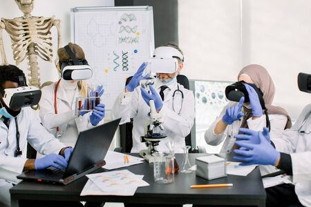 Scientists doctors in coats. gloves and wearing virtual reality glasses working in lab, making medical research. Biotechnology, chemistry, science, experiments and healthcare concept
