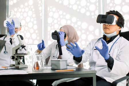 Team of scientists, Asian and Caucasian men, Muslim woman using virtual reality goggles for scientific research in laboratory, gesturing hands. Medicine, chemistry, microbiology, biotechnology Stock Photo