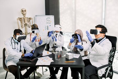 Team of multiethnic doctors, chemists, scientists in modern research laboratory using virtual reality goggles, gesturing, touching virtual reality screens, making notes. Human skeleton on background. Zdjęcie Seryjne
