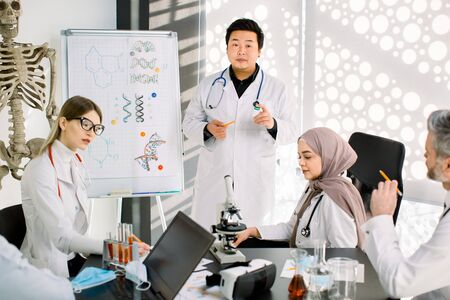 Biochemistry, pharmacology, drug industry, clinical trials. Young Asian doctor talks about the results of clinical trial of new medicine, having a meeting with his multiracial coworkers scientists.