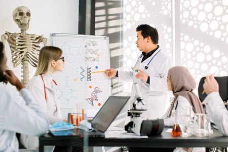 Handsome young Asian Korean male doctor standing near the clipboard and having lecture on the meeting at modern class, lab, explaining new biochemical structure of substance, gens or medicines Stock fotó