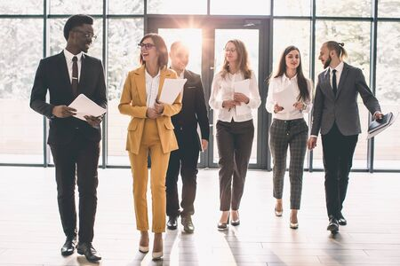 Business People Walking Toward Camera. Full length of group of happy young business people in formal wear having work meeting in modern office with large window Standard-Bild