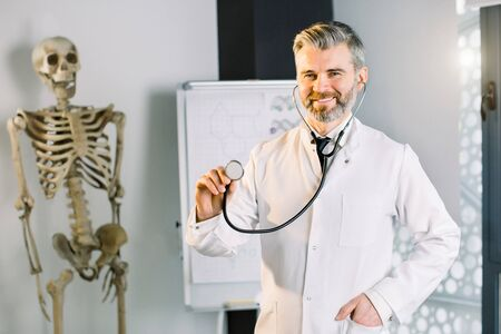 Male smiling doctor showing stethoscope for checkup to auscultate breath. Portrait of doctor smiling and standing with stethoscope at clinic. Human skeleton on the background Banco de Imagens