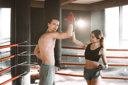 Girl boxer gives five tj her trainer in the middle of a boxing ring. Stock fotó