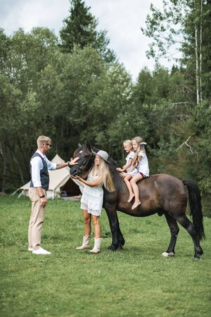 Happy young family with two children, wearing stylish casual boho clothes and beautiful horse in the forest or meadow. Summer camping tent, indian wigwam hut, Tipi on the background