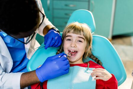 Cute smiling girl in at dentist sitting in armchair.