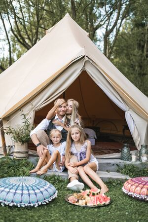 Cheerful positive family of four, mother, father and two daughters, having a picnic and eating watermelon outdoors in a sunny weather. Family in boho casual wear sitting near the tent tipi outdoors