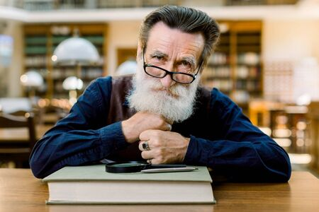 Close up portrait of smiling Caucasian senior bearded man in eyeglasses, sitting at the table with book, magnifying glass and pen, on vintage ancient library interior background.